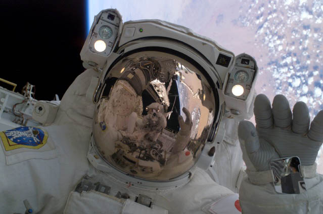 JAXA Astronaut Soichi Noguchi waves at his spacewalking crewmate, Astronaut Steve Robinson